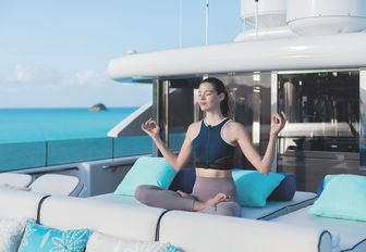 woman sits cross legged on cushions on foredeck of charter yacht titania and meditates