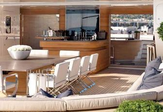 luxury yacht sundeck with dining, bar and selection of plants