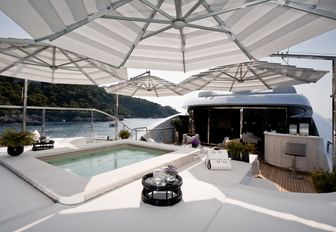 Sun deck with sun pads and pool on board luxury yacht 11/11