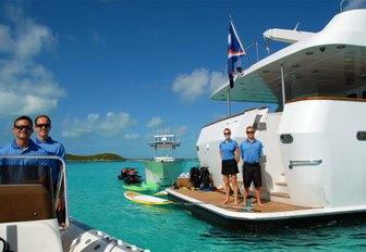 crew awaits on swim platform of luxury yacht Sweet Escape as tender departs