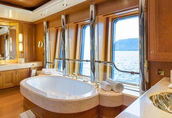 en-suite bathroom with a tub and large windows on board motor yacht BOADICEA