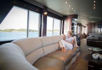 guest relaxes on the sofa in the main salon of charter yacht UNBRIDLED