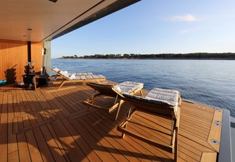 Beach club on luxury yacht PLANET NINE, with loungers lined up by the water