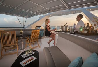 guest is served a drink at the sundeck bar aboard superyacht UNBRIDLED