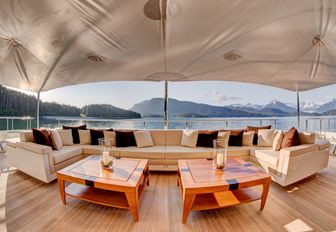 Ivory coloured sofa forms alfresco lounge on main deck aft of charter yacht Party Girl