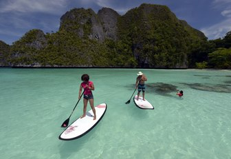 two people paddle board in the crystal clear waters of Raja Ampat