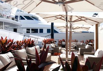 Cafe area with superyacht in background at FLIBS