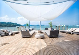 sofas and sunloungers under a canopy shade on board motor yacht SALUZI