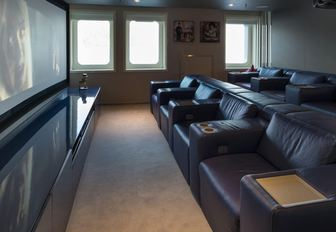 Indoor cinema room onboard 72m M/Y SERENITY, rows of plush leather chairs facing wall mounted screen.