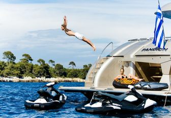 male charter guest dives of swim platform aboard luxury yacht PANDION as female guest watches