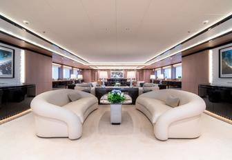 white sofas form a seating area in the main salon of luxury yacht O'Ptasia