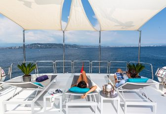 charter guests relax on the sun loungers aboard motor yacht DXB