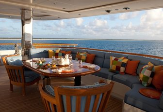 colourful upholstery and table in aft deck lounging area aboard charter yacht OASIS