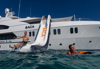 Man coming down large water slide from side of Superyacht BACA