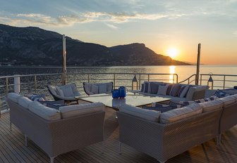 Aft deck exterior seating arrangement onboard M/Y SERENITY, overlooking elevated terrain and sunset over sea
