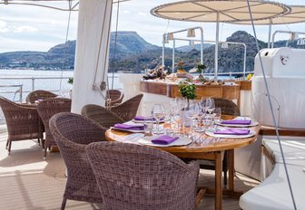 Dining area on superyacht SHERAKHAN sundeck, with two tables and spa pool in background
