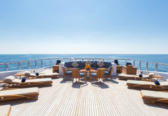 seating area and sun loungers line up on the sundeck of charter yacht WHEELS
