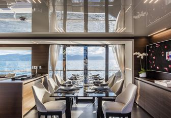 formal dining area flanked by floor-to-ceiling windows on board charter yacht December Six