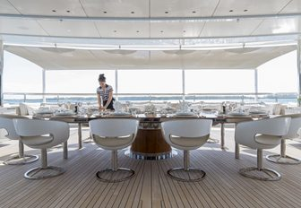 crew member prepares table for dinner on the dining deck aboard charter yacht NAUTILUS