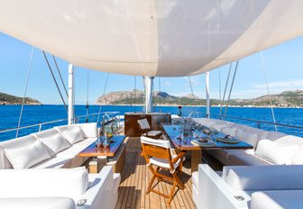 seating and casual dining area on the flybridge of charter yacht Q with Bimini