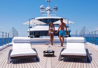 guests walk towards sun loungers of the foredeck of luxury yacht 11/11