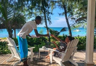 man serves woman drink on outdoor terrace of thanda island, a private island retreat off the coast of tanzania, with views over the ocean through palm trees in background