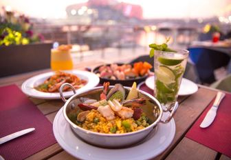 Seafood dishes on table with drinks located on terrace of Aquarium, with hotel in background