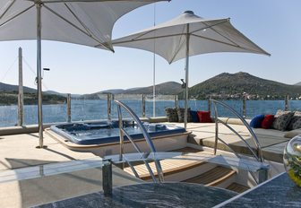 spa pool surrounded by sun pads and umbrellas on the sundeck of luxury yacht Mary-Jean II