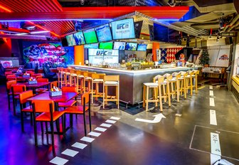 small square tables and large bar with bar stools in colourful sports bar Stars 'N' Bars
