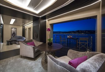 luxe seating area opens onto terrace on board charter yacht Mogambo