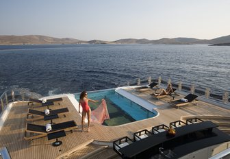 Model prepares for a dip in luxury superyacht Alfa Neros's swimming pool while sailing down exotic ocean looking back onto the island