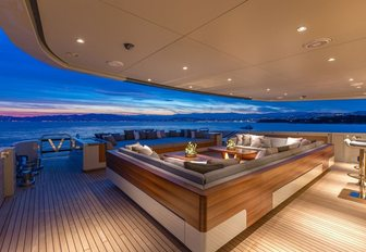 A nighttime shot of the sofa seating on the exterior of superyacht VERTIGE