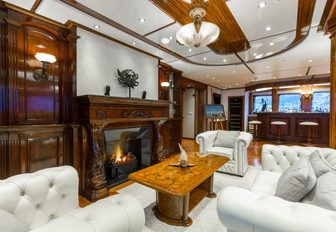 fireplace surrounded by plush white seating on board luxury yacht LEGEND