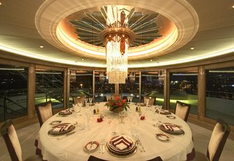 circular dining table with panoramic views and glittering chandelier on board luxury yacht AMARYLLIS