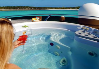 jacuzzi on superyacht with charter guest enjoying cocktail