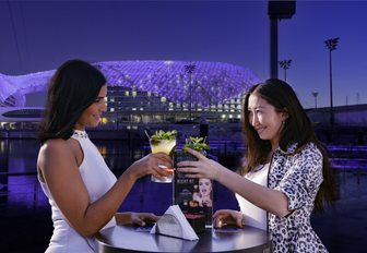 Women at outdoor table at Aqaurium, Yas Island clinking drinks with views of Yas Viceroy in backround at nighttime