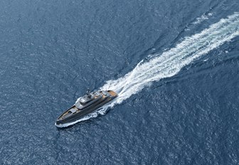 Aerial image of motor yacht ERICA.  Her impressive grey exterior is central with a stream flowing behind