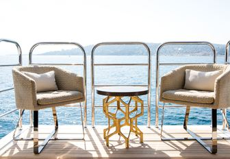 table and chairs on side balcony of luxury yacht BLUSH