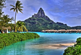 luxe over-water bungalows in Bora Bora against mountain backdrop