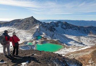 hikers take in lake on the Tongariro Crossing in Tongariro National Park, New Zealand