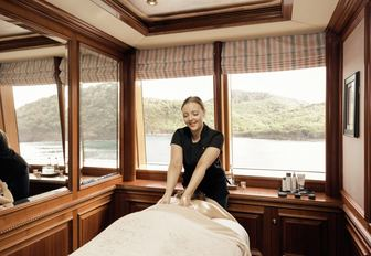 spa therapist gives guest a massage on motor yacht titania, with view of thailand in background