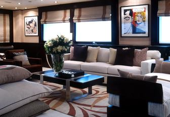 Sofas and table on Illusion I yacht with windows and artwork behind