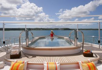 5 metre pool onboard yacht charter AMARYLLIS, female charter guest taking in the view, with sunloungers in foreground.