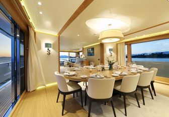 formal dining area flanked by large windows in the main salon of motor yacht SOLIS