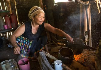 Local lady of Ngada village cooking in thatched roof cottage