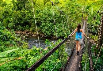 oung woman walking on suspension bridge over Wainibau stream, Lavena Coastal Walk, Taveuni Island, Fiji.