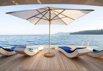 sun beds line up on the large swim platform aboard charter yacht O'PTASIA