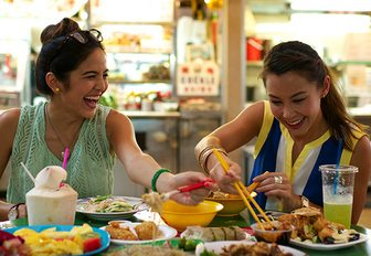 Two charter guests enjoying some Singapore street food