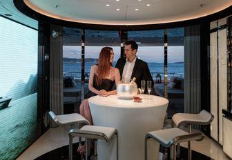 guests enjoy champagne at the bar on board motor yacht MYSKY