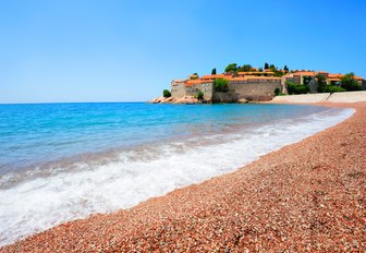 pebbly beach and blue waters of Sveti Stefan Island in Montenegro